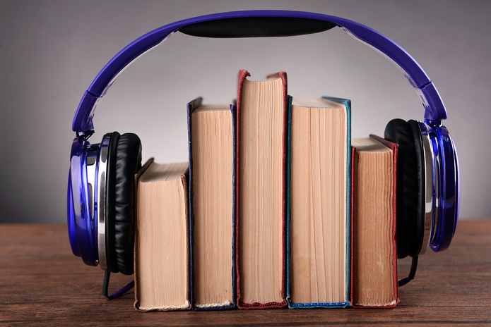 five books and blue headphones