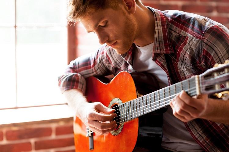 blonde man in shirt playing guitar