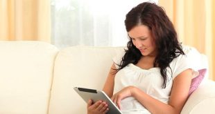 young woman sitting on the couch using her iPad